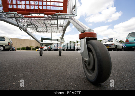 Shopping cart in parking lot, surface level view - Stock Photo