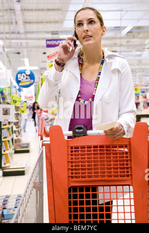 Woman using cell phone in supermarket - Stock Photo