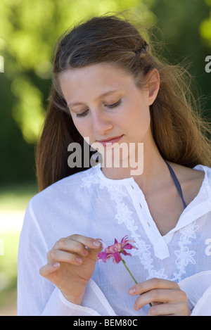 Young woman plucking petals from flower - Stock Photo