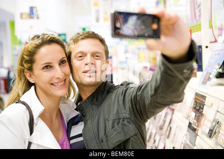 Couple taking self portrait with demo photophone in store - Stock Photo