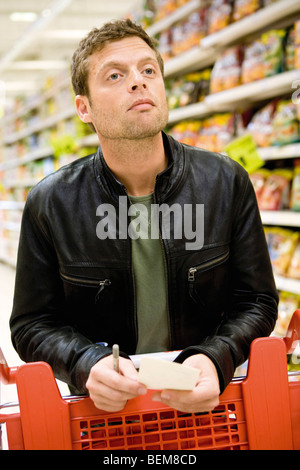 Man in supermarket with shopping list - Stock Photo