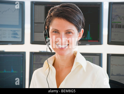 Female trader on headset - Stock Photo
