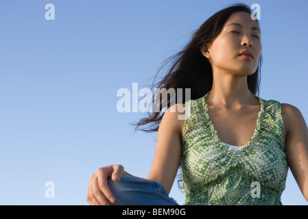 Woman sitting outdoors with eyes closed - Stock Photo
