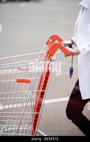 Shopping cart being pushed across parking lot - Stock Photo