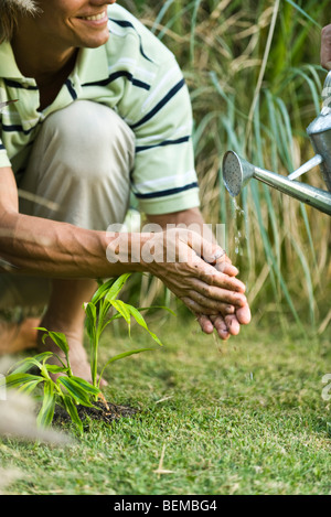 Watering can pouring water, man washing hands - Stock Photo