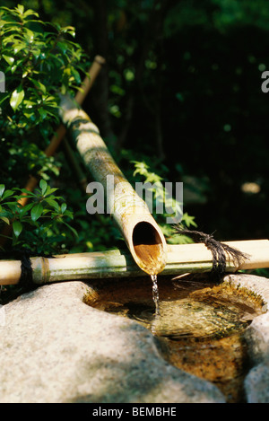 Water trickling from bamboo pipes into stone wash basin, Japan - Stock Photo