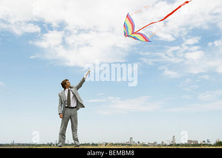 Businessman with arm raised flying kite in field - Stock Photo
