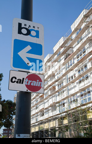 A low angle view of BART and Caltrain road signs by a scaffolded condo. Millbrae, California, USA - Stock Photo
