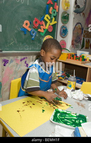 African-American preschool boy finger painting in the classroom - Stock Photo