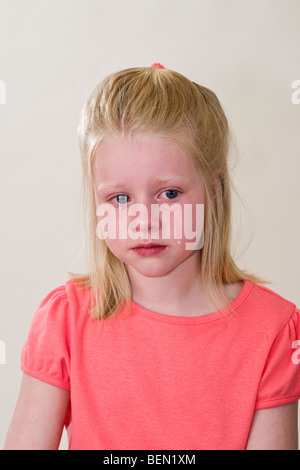 6 year old girl crying with deep sadness.grief facial expression emotional emotions emotion anger angry resentment - Stock Photo
