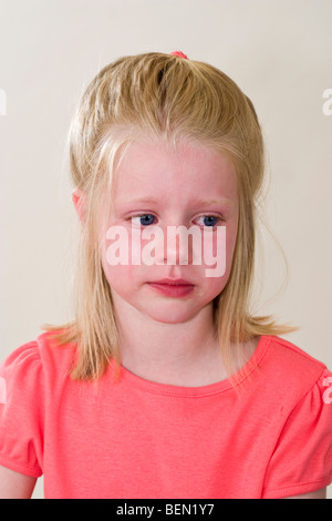 Closup young Caucasian 6 year old girl crying cries with deep sadness grief pain facial expression emotional emotions - Stock Photo