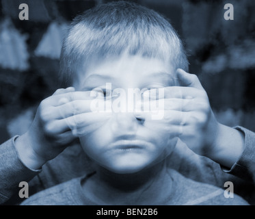 A small boy with eyes covered in an ethereal double exposure. Autism and blindness concepts - Stock Photo