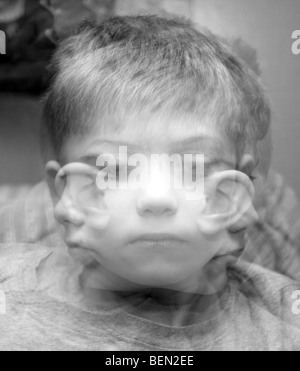 A Triple exposure depicting a small boy looking in three different directions - Stock Photo