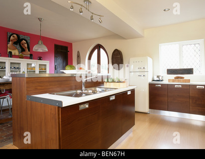 Pink wall in large modern cream kitchen with dark wood units and double stainless-steel sinks in island unit