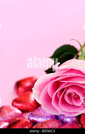 Pink rose with Valentine's chocolates wrapped in red and purple foil - Stock Photo