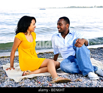 Young romantic couple looking at each other sitting on beach - Stock Photo