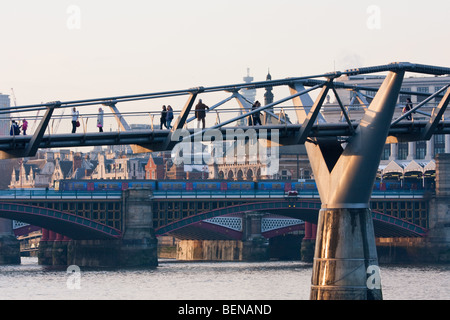 People crossing Millennium Bridge with River Thames & Blackfriars Station behind. - Stock Photo