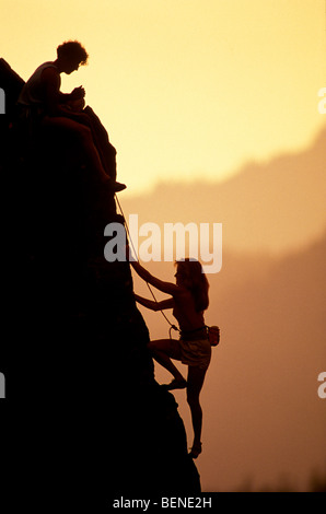 A woman climber ascends the last pitch on a rock climb. Her climbing partner belays her from above. - Stock Photo