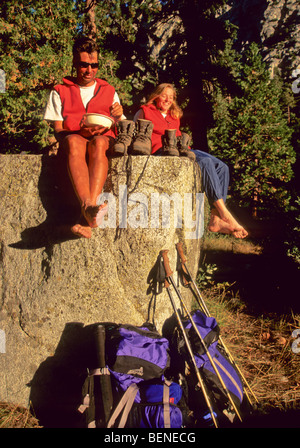 Couple resting on rock. - Stock Photo
