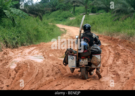 Heavily packed motorbike rider with surfboard riding on bike through mud of dirt road during rainy season, Gabon, - Stock Photo