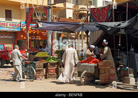 Street vendor dressed in jalabiya / galabiya selling fruit and vegetables at market stall in Luxor, Egypt, North - Stock Photo