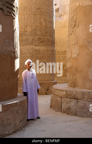 Man wearing traditional jalabiya among columns showing hieroglyphics in the Karnak temple complex, Luxor, Egypt, - Stock Photo