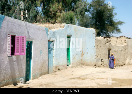 Bedouin woman in street with traditional houses in the Farafra Oasis in the Western desert, Egypt, North Africa - Stock Photo
