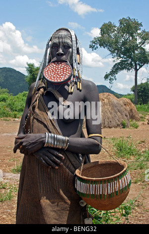 Close up of tribal Mursi woman with large clay plate in pierced lower lip, Omo Valley, Ethiopia, East Africa - Stock Photo