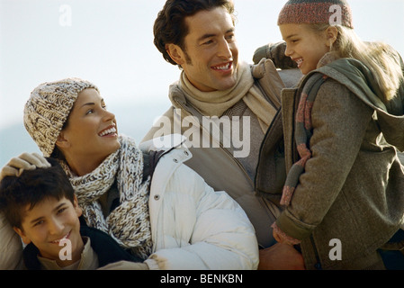 Family outdoors, father carrying daughter, mother ruffling son's hair - Stock Photo