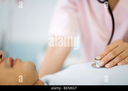 Nurse listening to patient's heart using stethoscope, cropped - Stock Photo