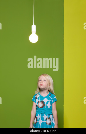 Little girl staring up at illuminated light bulb suspended overhead - Stock Photo