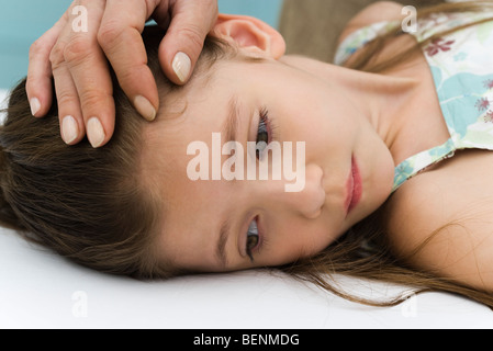 Little girl lying on back, parent stroking her forehead, cropped - Stock Photo