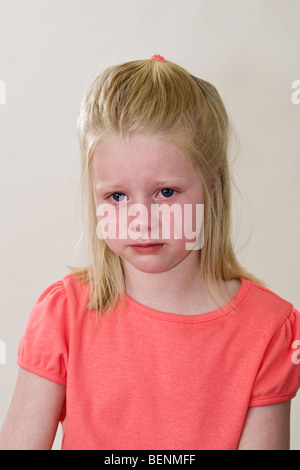 Caucasian 6 year old girl crying with deep sadness abandonment abandoned crushed facial expression deeply felt  - Stock Photo