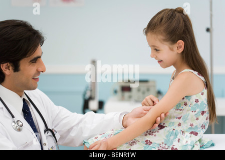 Friendly doctor examining little girl's arm - Stock Photo