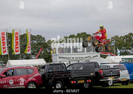 Kangaroo Kid alias Matt Coulter quad stunt bike in mid air over parked cars Moreton Show September 2009 UK - Stock Photo
