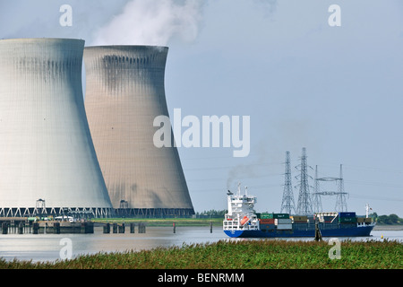 Container ship on the river Scheldt in front of the cooling towers of the nuclear power plant at Doel, Belgium - Stock Photo