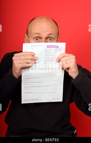 Man holds up a clean CRB Enhanced Disclosure form showing no criminal convictions or endorsements - Stock Photo