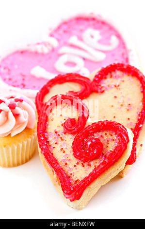 Homemade baked shortbread Valentine cookies and cupcake with icing on white background