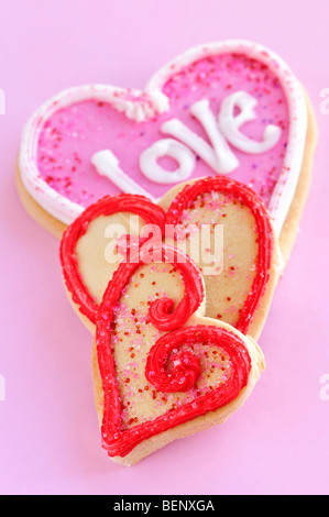 Homemade baked shortbread Valentine cookies with icing on pink background