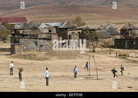 Children playing football in Basotho / Basuto village showing stone huts with thatched roofs in Lesotho, Africa - Stock Photo