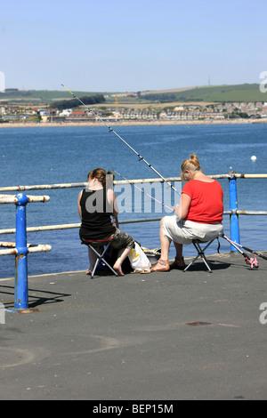 Two females Sea fishing off the harbor entrance Weymouth Dorset England - Stock Photo