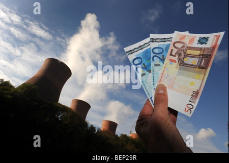 Energy price increases depicted with Euro money and power station - Stock Photo