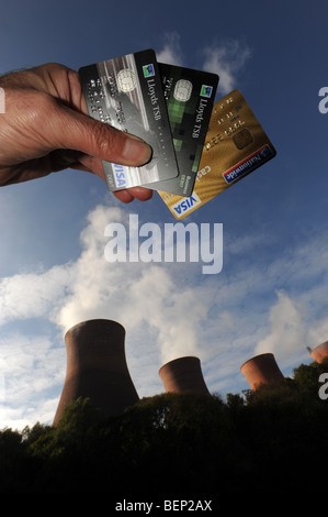Energy price increases depicted with credit cards and power station - Stock Photo