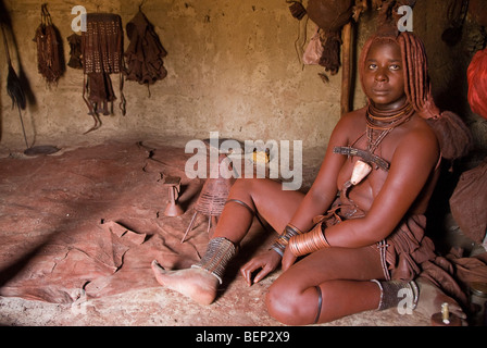 Himba woman in her hut in a village near Epupa Falls, Namibia, Africa. - Stock Photo