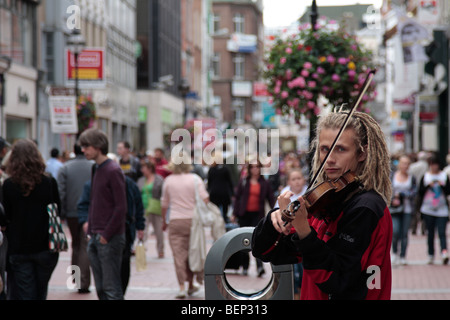 A busker plays the fiddle on Grafton Street in Dublins city centre Ireland - Stock Photo