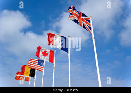 National flags on flagpoles flying in the wind against cloudy sky - Stock Photo