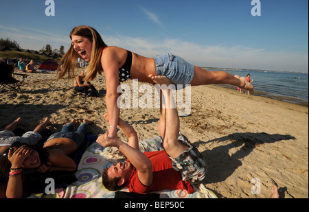 A young man and woman who also happen to be brother and sister playing together on beautiful white sandy beach - Stock Photo