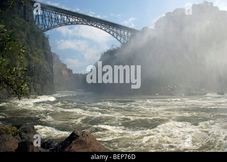 Bridge over the Zambezi river between Zambia and Zimbabwe, covered in spray of the Victoria falls, Southern Africa - Stock Photo