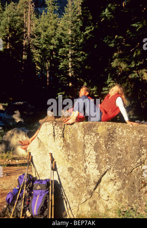 Couple resting on rock in the sun. - Stock Photo