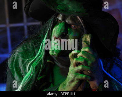 Portrait of a scary old witch illuminated with eerie blue green lighting - Stock Photo